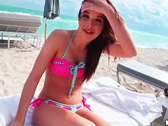 Beautiful and sexy dark-haired minx rests on the beach